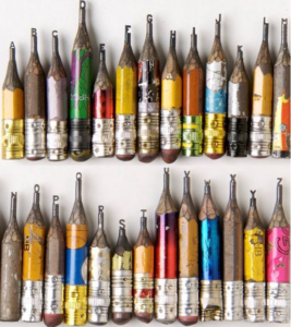 A variety of pencils sharpened until they hardly have any grip, If you look closely where the lead tip should be has been replaced with a small letter of the alphabet, organised from A through to Z.