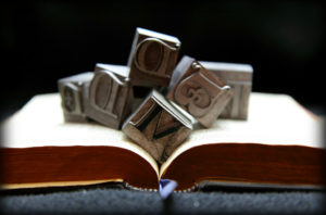 Metal letters (that could be old fashioned stamps) sit in a jumble atop an open book.