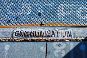 A pressed metal sign with the word communication burnt into it