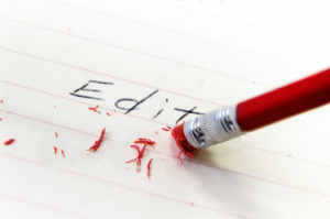 red pencil with a red erase at the end about to rub out the word Edit written in pencil on piece of lined paper