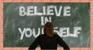 A woman standing in front of a green chalkboard with the words believe in yourself written on it in white chalk