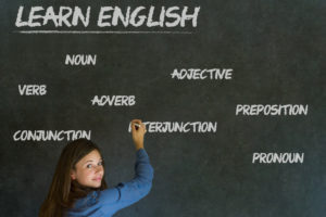 Woman standing in front of a blackboard with the words Learn English, adverb, very, adjective etc, written on the board in white chalk