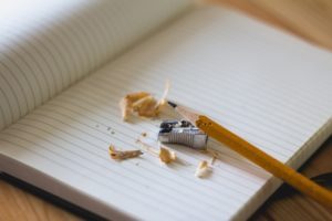 pencil leaning on a notebook and a metal sharpener surrounded by pencil shavings